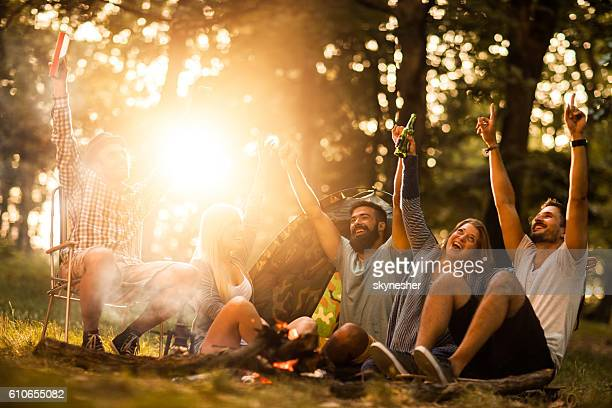 Cheerful group of friends having fun on camping in nature.