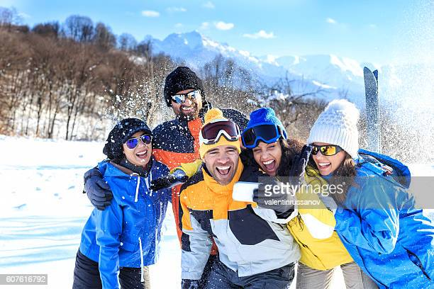 Cheerful group of friends making selfie in the snow mountain