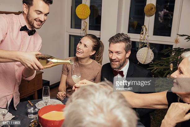 Cheerful group of friends opening champagne on New Year's Eve