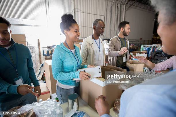 cheerful group of volunteers working together - food bank stock pictures, royalty-free photos & images