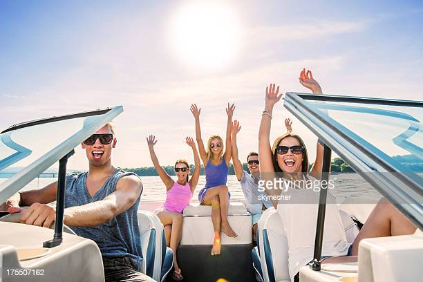 cheerful group of young people enjoying in speedboat ride. - five people stock pictures, royalty-free photos & images