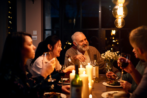 Cheerful guests at dinner table listening to friend and drinking wine - gettyimageskorea