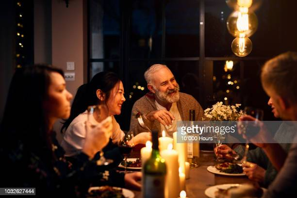 cheerful guests at dinner table listening to friend and drinking wine - warmes abendessen stock-fotos und bilder