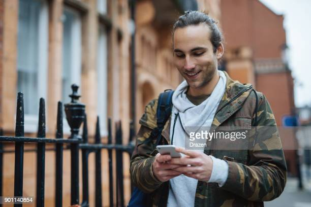 cheerful guy walking in the street and using smart phone - camouflage clothing stock pictures, royalty-free photos & images
