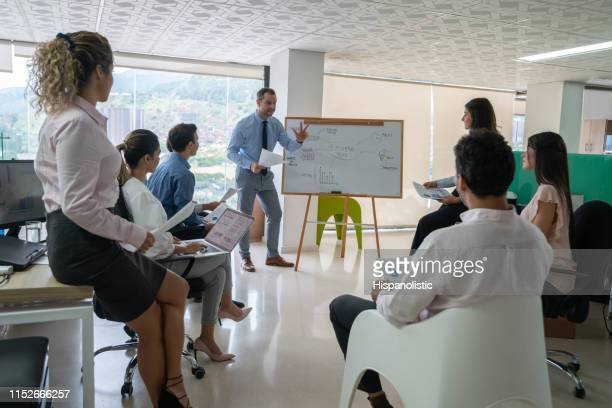 cheerful handsome business leader in a meeting addressing his team - hispanolistic stock photos and pictures