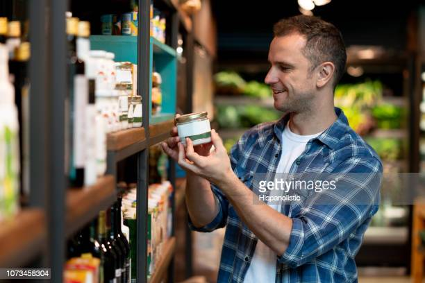 Cheerful handsome latin american man choosing products from shelf at a grocery store smiling