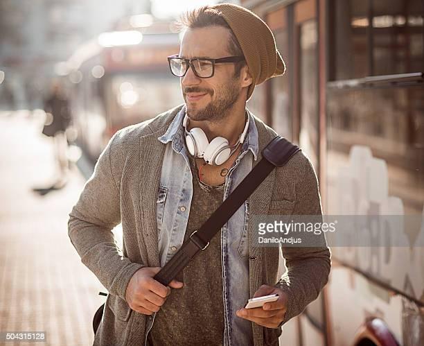 Allegro un bell'uomo usando il suo smartphone all'aperto