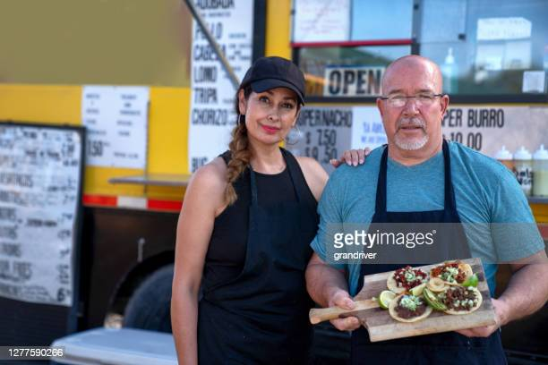 cheerful handsome middle aged mexican couple in front of their food truck smiling and displaying a platter of their delicious street tacos with carne asada, tacos al pastor and carnitas ready to eat - serving food and drinks stock pictures, royalty-free photos & images