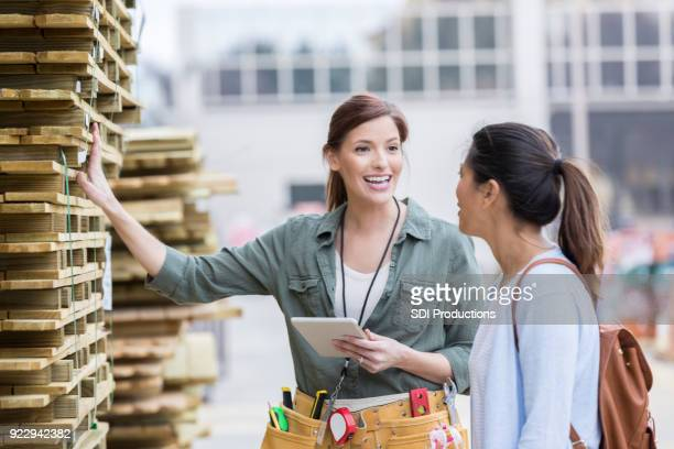Cheerful hardware store employee discusses wooden pallets with customer