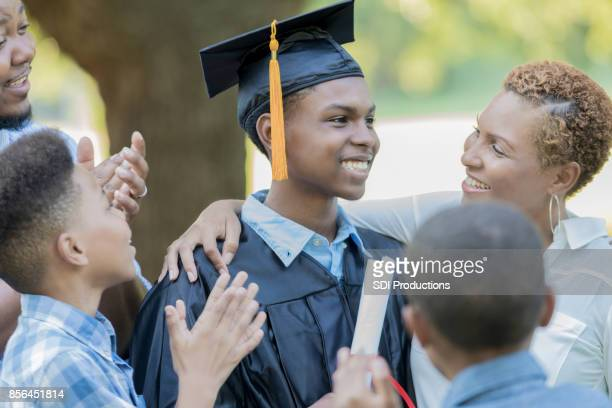 Cheerful high school graduate with his family