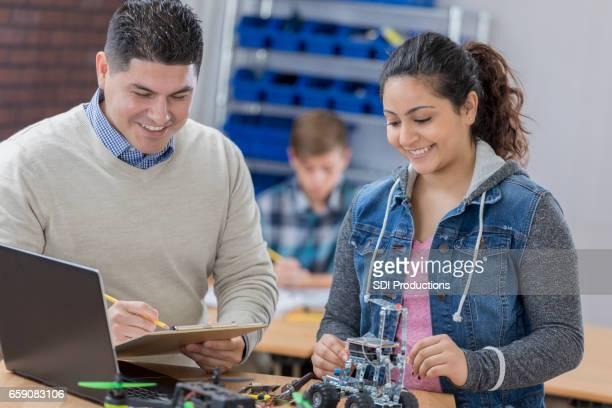 Fröhliche High-School-Lehrer hilft Studenten mit Projekt