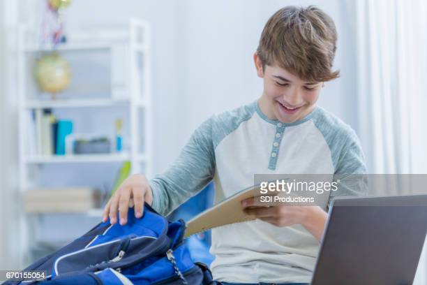 Cheerful high schoolboy unpacks backpack at home
