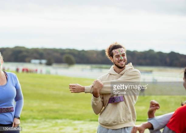 cheerful hipster man stretching before outdoor event - warming up stock pictures, royalty-free photos & images
