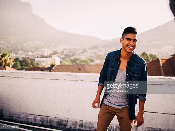 Cheerful hipster teenager boy laughing on a rooftop at sunset