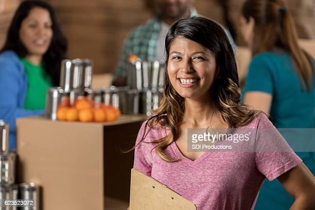 Cheerful Hispanic food bank organizer at charity event
