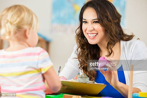 Cheerful Hispanic teacher shows heart shaped block to blonde preschooler