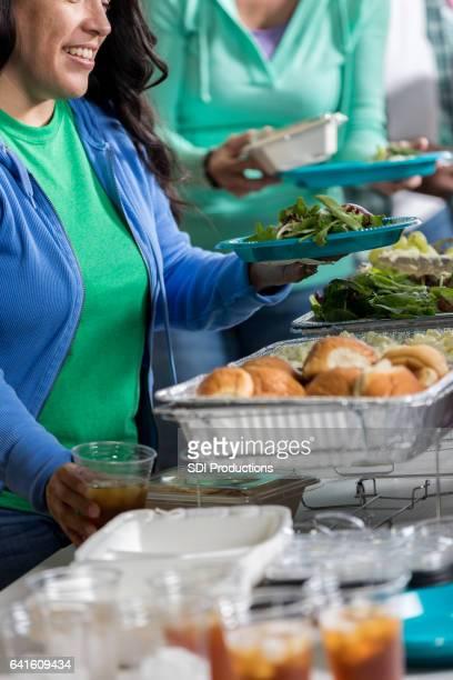 Vrolijke Hispanic vrouw ontvangt maaltijd in dakloze onderdak