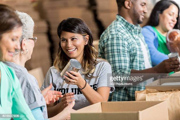 cheerful hispanic woman volunteers at food bank - donation stock photos and pictures