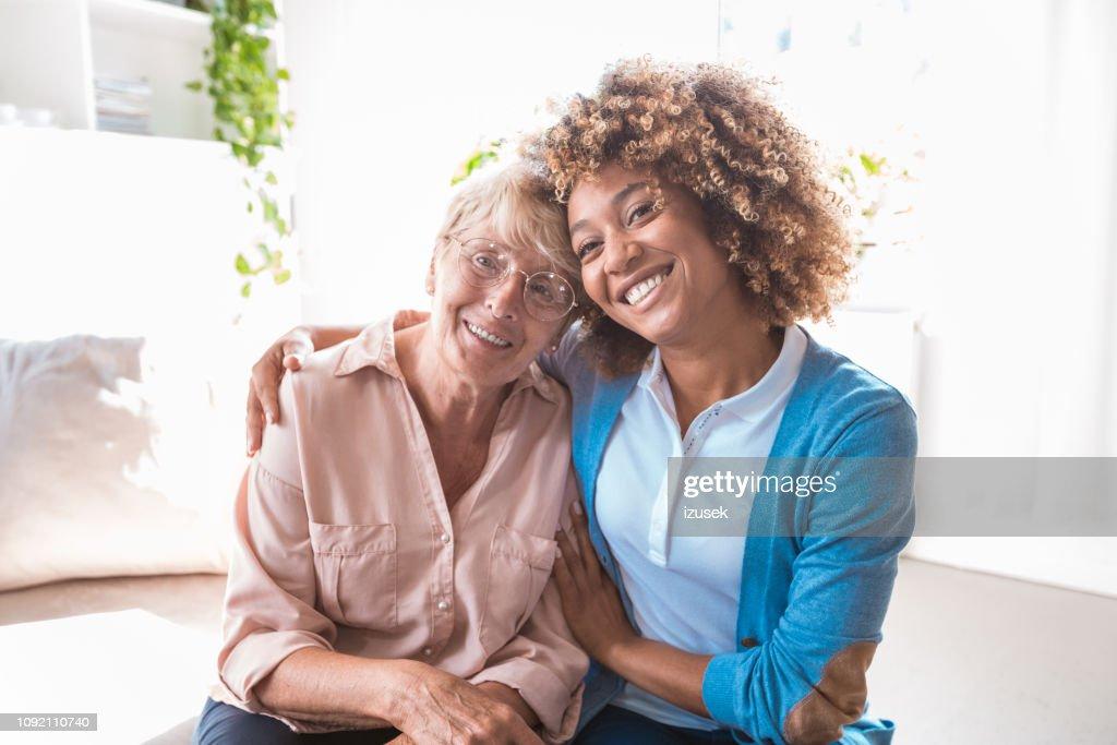 Cheerful home caregiver embracing senior woman : Stock Photo