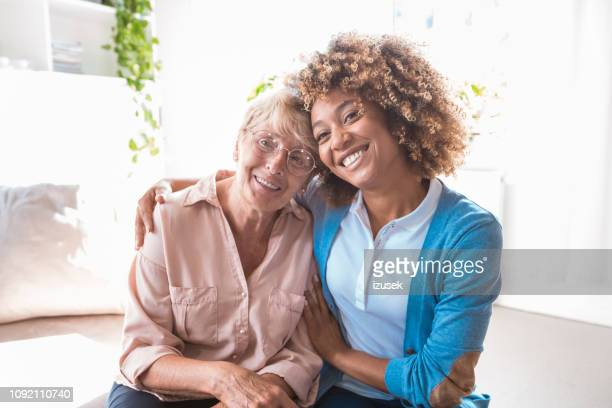 Cheerful home caregiver embracing senior woman