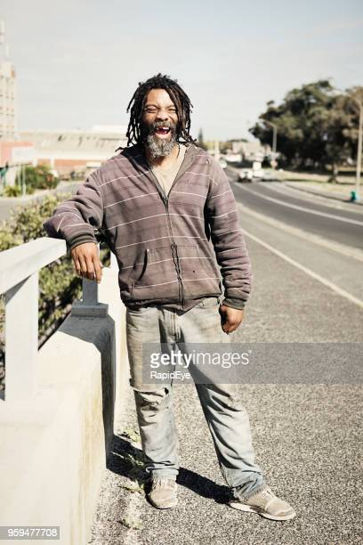 cheerful homeless man stands on a bridge - homeless person stock pictures, royalty-free photos & images