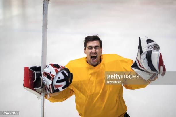 vrolijke ijshockey doelman schreeuwen terwijl de viering van zijn team de overwinning in een ijsbaan. - ijshockeytenue stockfoto's en -beelden
