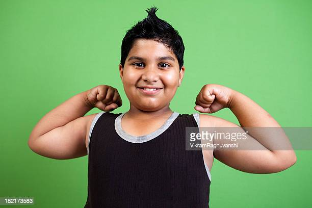 Cheerful Indian Boy showing his muscles