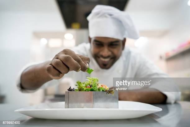 Cheerful indian chef making a salad to serve as appetizer