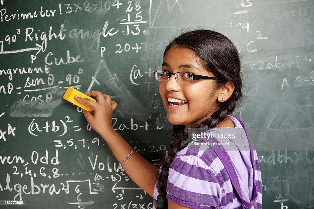 Cheerful Indian Girl Student Erasing Mathematics Problems from Greenboard Blackboard : Stock Photo