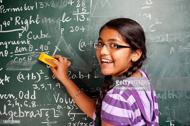 cheerful indian girl student erasing mathematics problems from greenboard blackboard - girls stock pictures, royalty-free photos & images