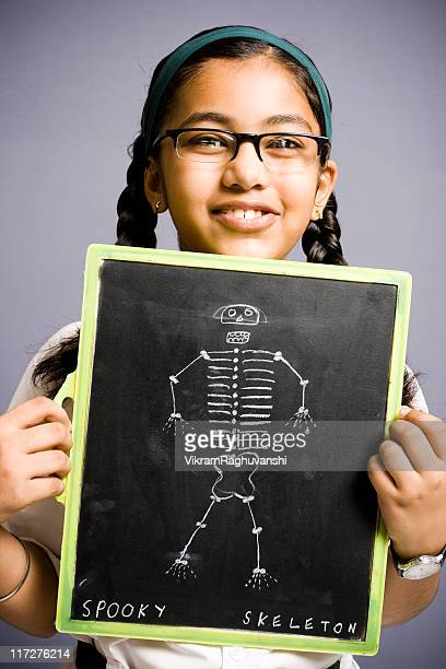 Cheerful Indian school girl showing black board with skeleton drawing