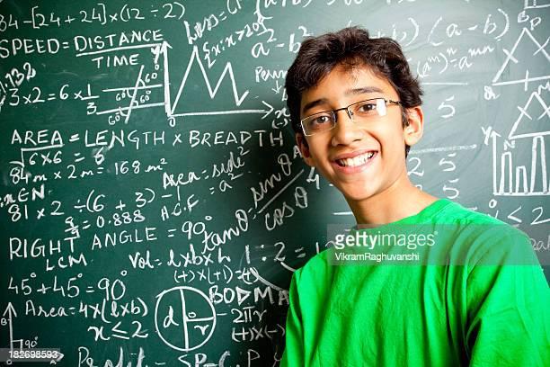 陽気なインドのティーンエイジャー少年スチューデントに数学問題水平