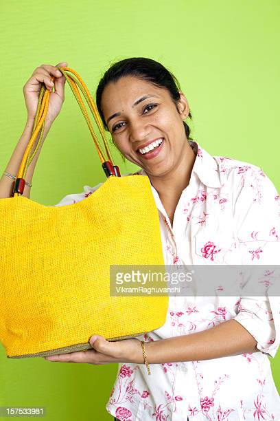 Cheerful Indian Woman holding shopping bag Vertical Lifestyle Shot