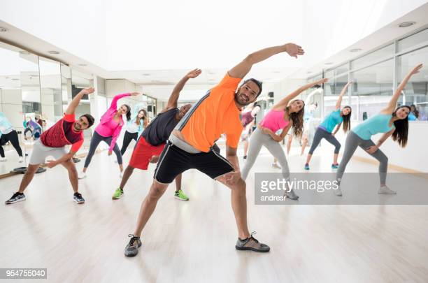 cheerful instructor guiding his class to strecth at the gym - aerobics stock pictures, royalty-free photos & images