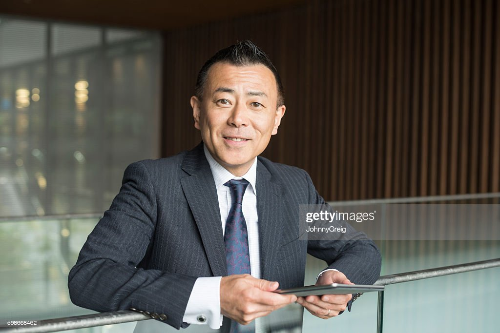 Cheerful Japanese businessman with digital tablet, smiling : ストックフォト