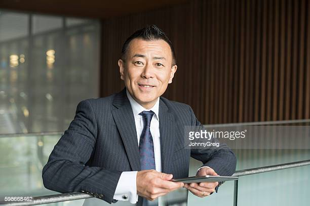 Cheerful Japanese businessman with digital tablet, smiling
