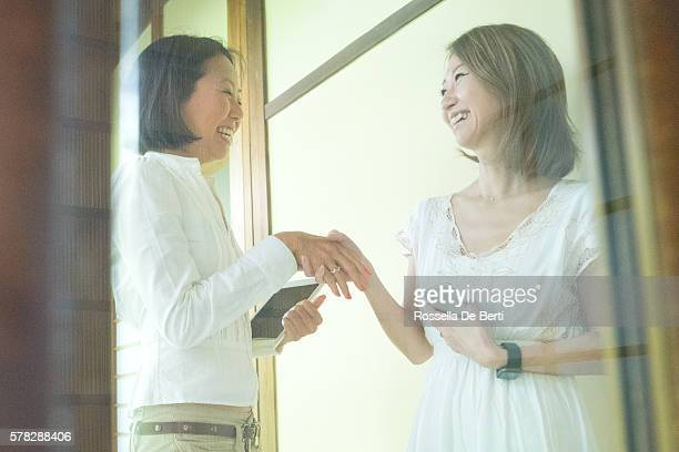 Cheerful Japanese businesswomen shaking hands