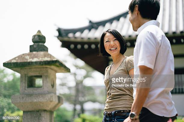 Cheerful japanese couple at the temple, front view