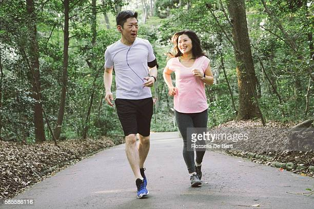 cheerful japanese couple running outdoors in a park - 走る ストックフォトと画像