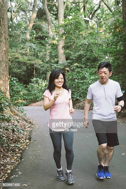 Cheerful Japanese couple running outdoors in a park