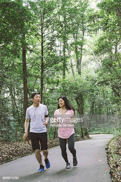 cheerful japanese couple running outdoors in a park - lypsekyo16 stock pictures, royalty-free photos & images