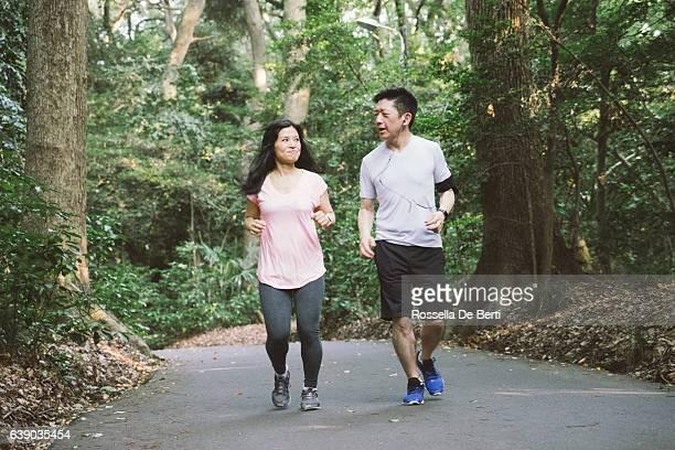 Fröhlich Japanisches Paar Laufen im Freien in einem park
