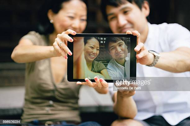Cheerful Japanese couple taking selfie at the temple