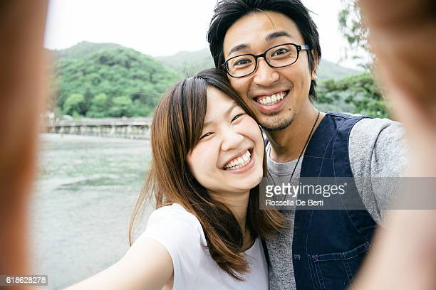 Cheerful Japanese couple taking selfie outdoors in a park