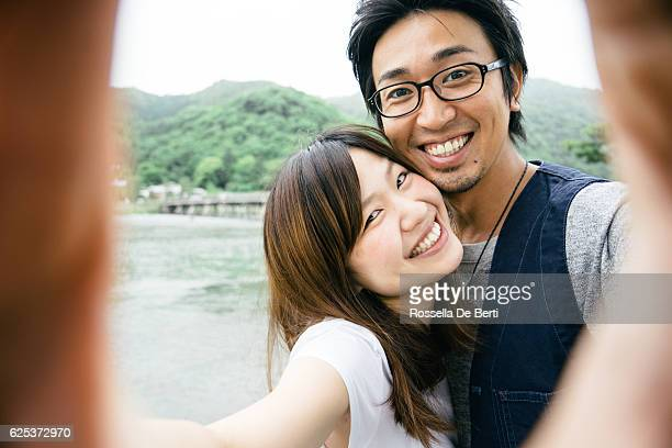 cheerful japanese couple taking selfie outdoors in a park - photographing self stock pictures, royalty-free photos & images