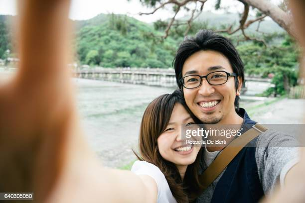 cheerful japanese couple taking selfie outdoors in a park - 撮影テーマ ストックフォトと画像