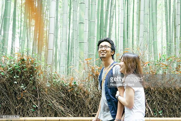 Cheerful Japanese couple walking through bamboo forest