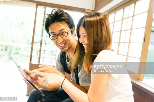 Cheerful Japanese friends using tablet indoors