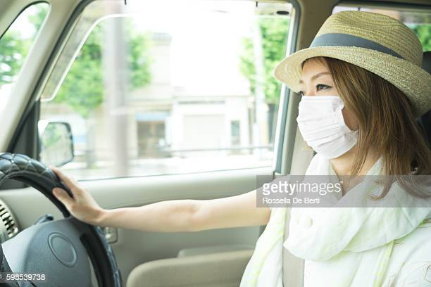 Cheerful Japanese woman driving car wearing anti-pollution mask