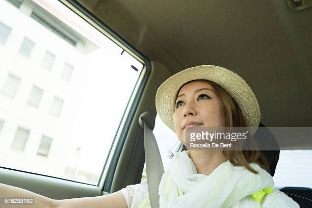 Cheerful Japanese woman driving car wearing